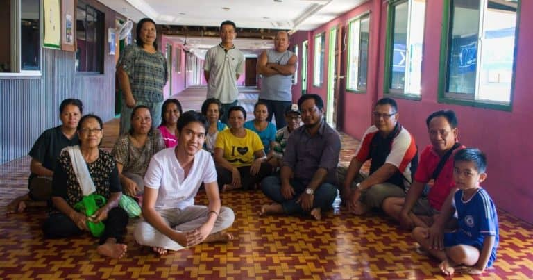 Albert with his community and the film protagonist, Tony (in striped purple shirt) in his community's longhouse